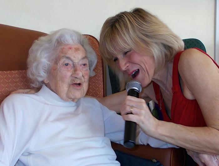 Photo of senior and performer both singing