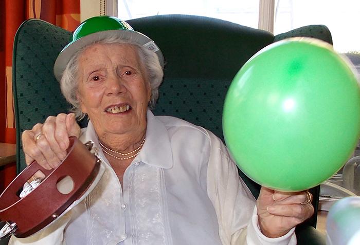 Photo of elder holding a balloon and tamborine